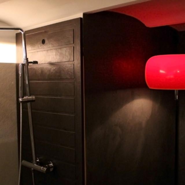 Bagno di un hotel in microcemento con luce rossa e doccia
