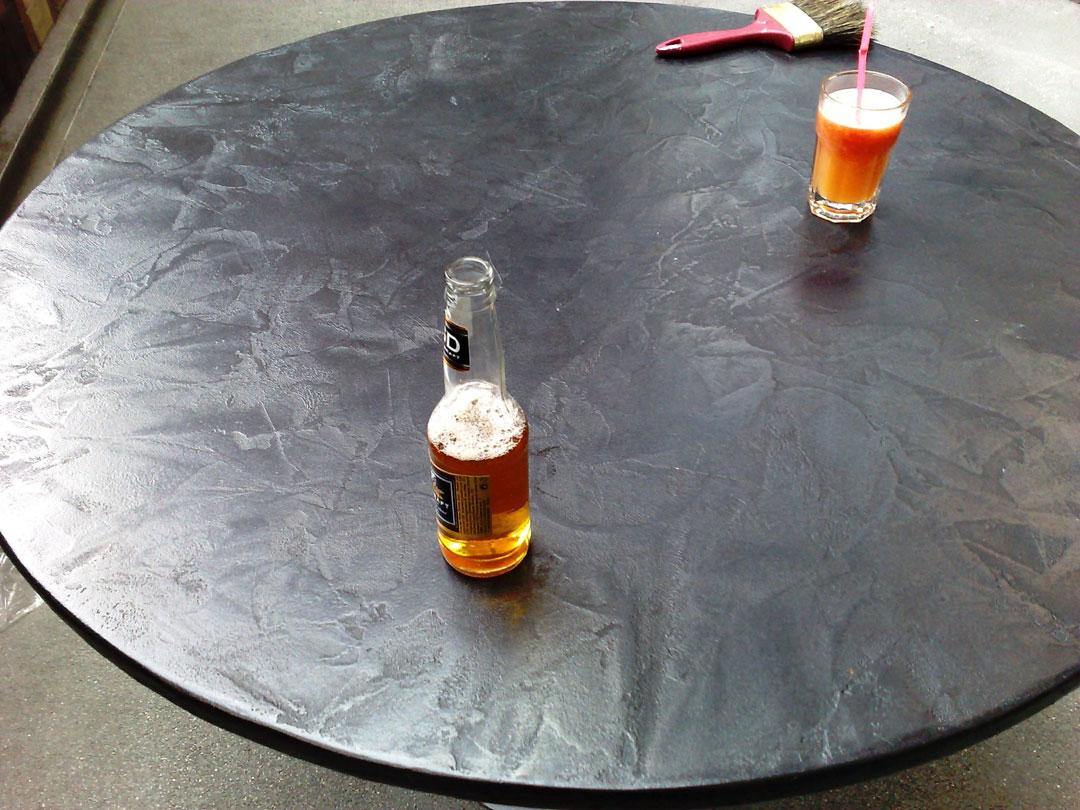 Tavolo in microcemento scuro con bibite sopra