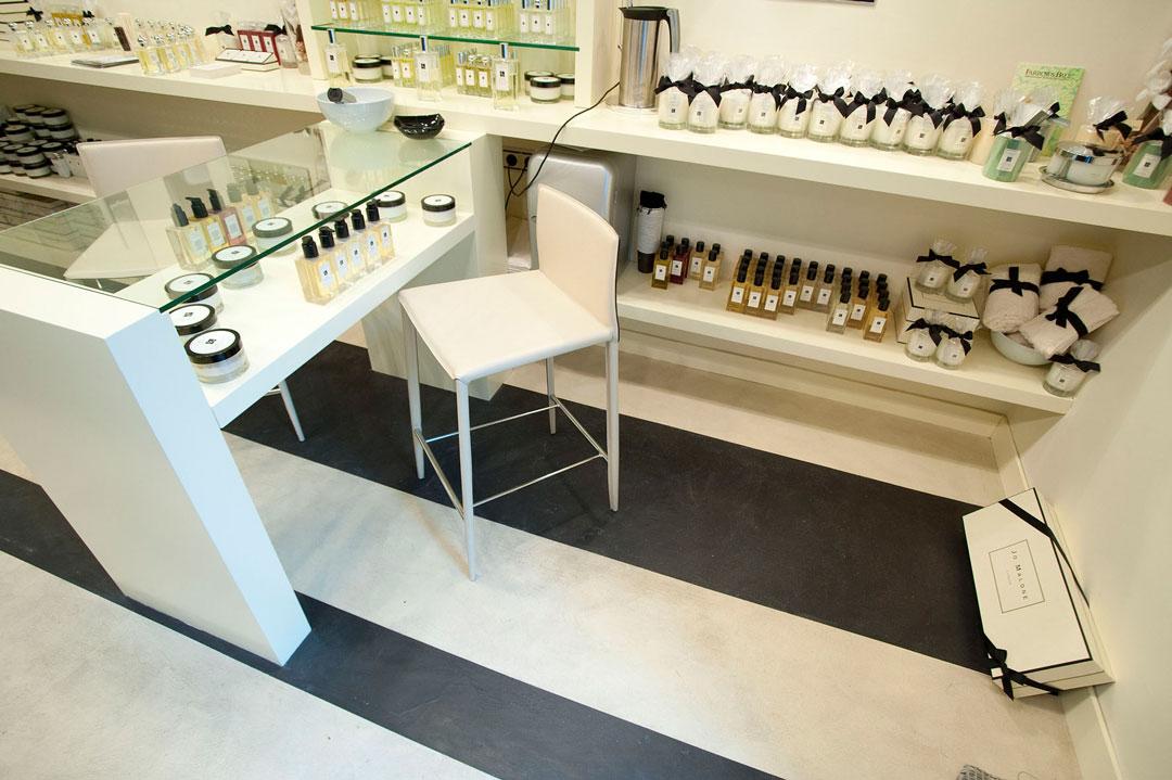 profumeria con profumi e cosmetici in microcemento bianco