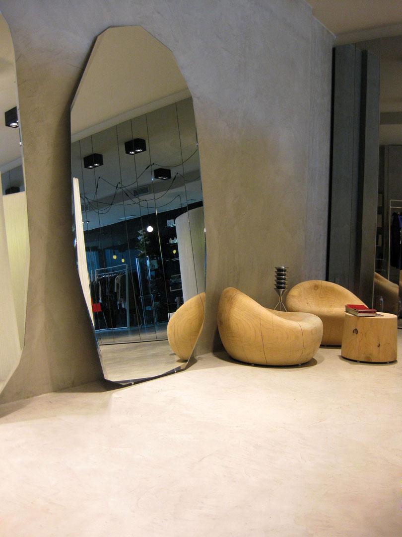 commerciale di abbigliamento con poltrone in legno e specchi