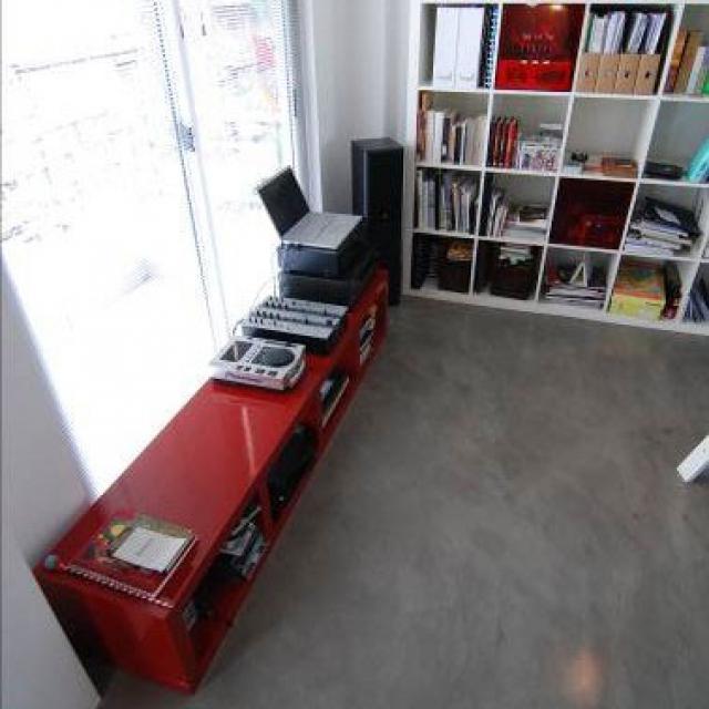 Pavimento in microcemento con mobile rosso e mensole bianche