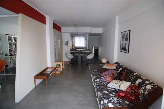 Pavimento in microcemento grigio con mobili bianchi