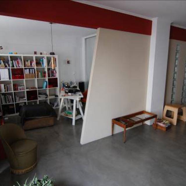 Pavimento in microcemento grigio con mobili da studio bianchi