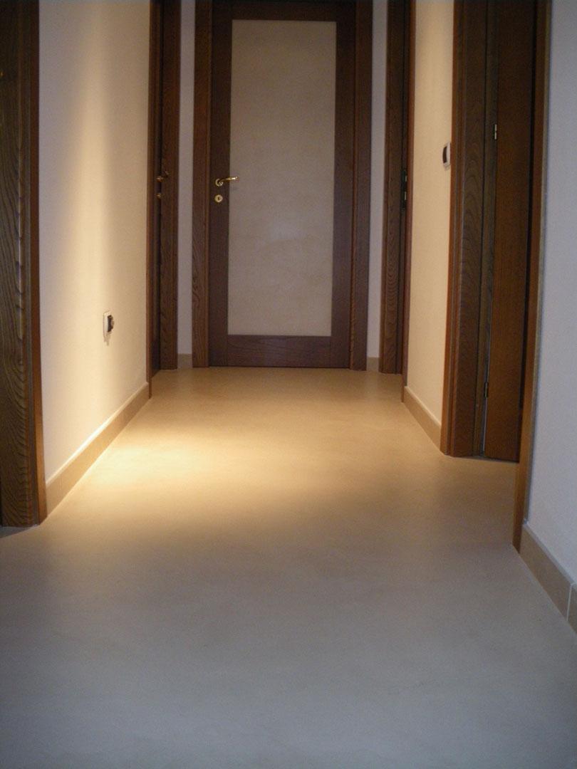 Pavimento in microcemento per ingresso con porte in legno