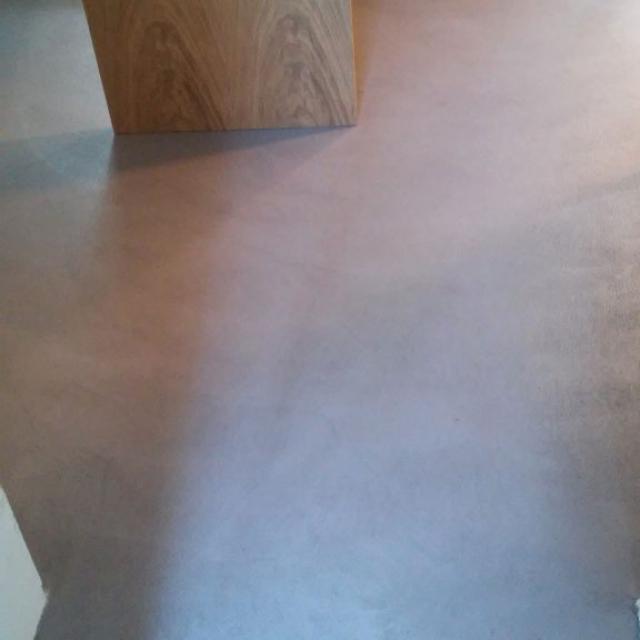 Pavimento in microcemento con colonna in legno
