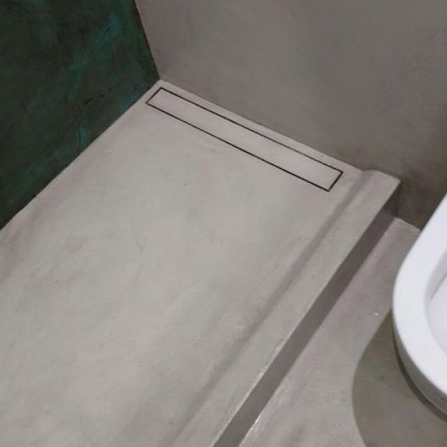 Bagno con piatto-doccia in microcemento