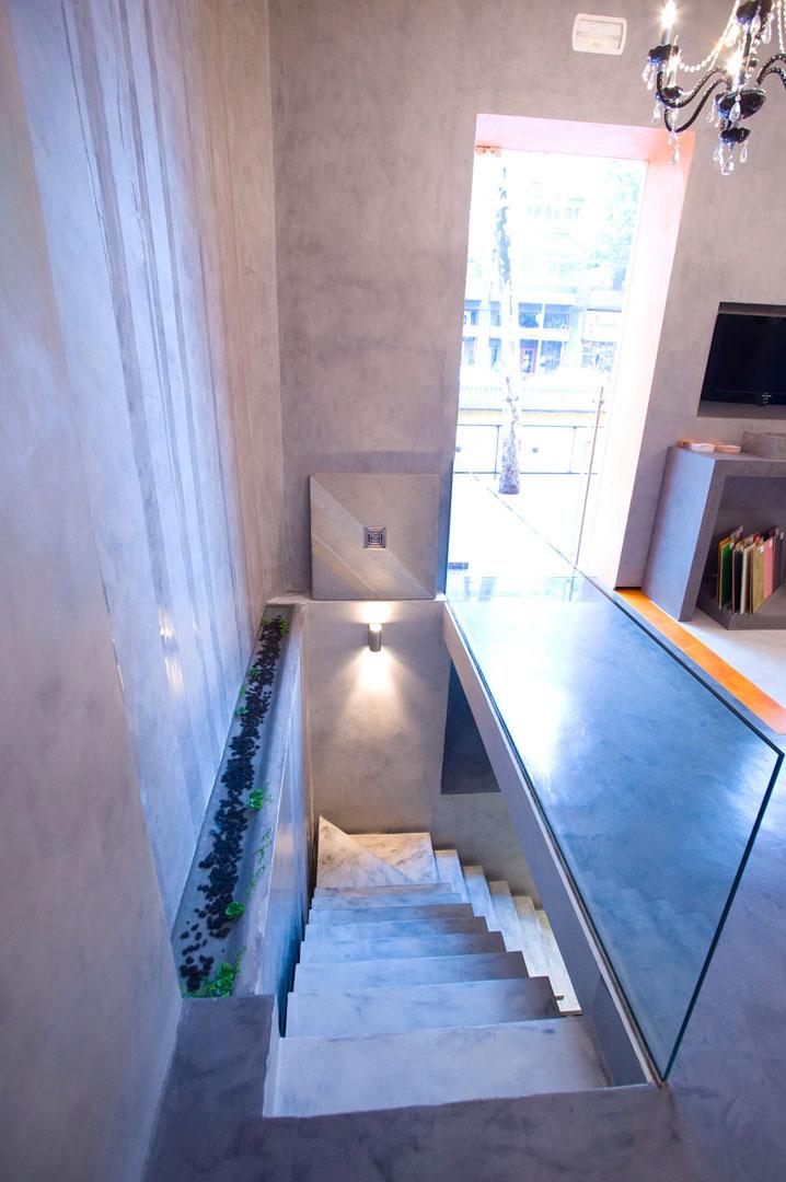 Scala in microcemento chiara con pareti grigie