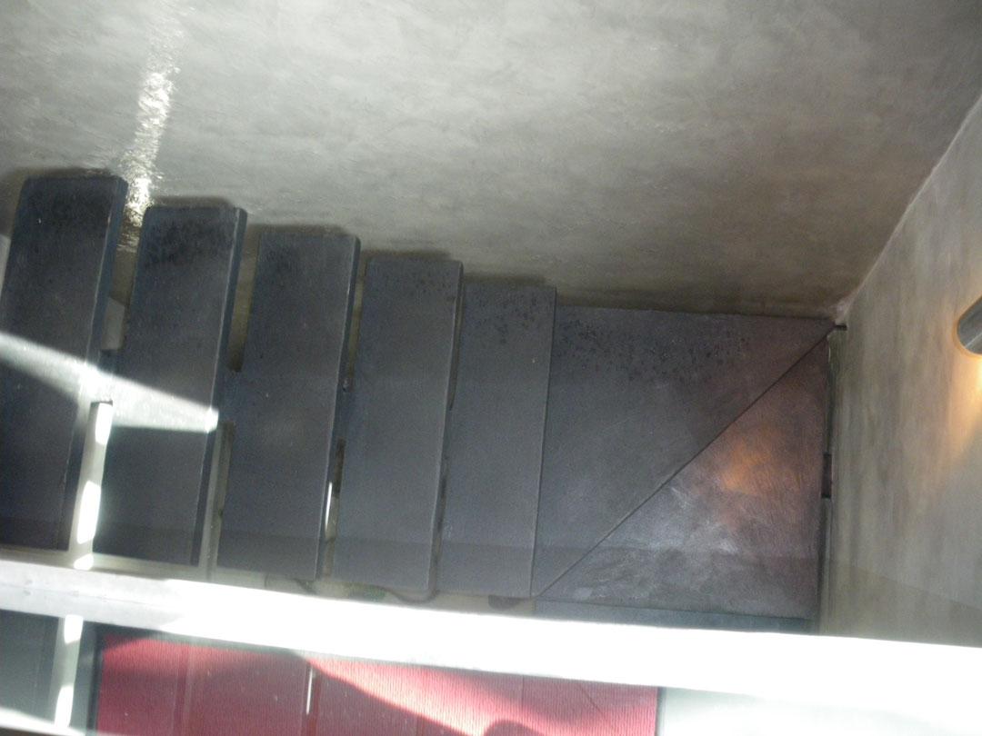 Scala scura in microcemento con pareti grigie