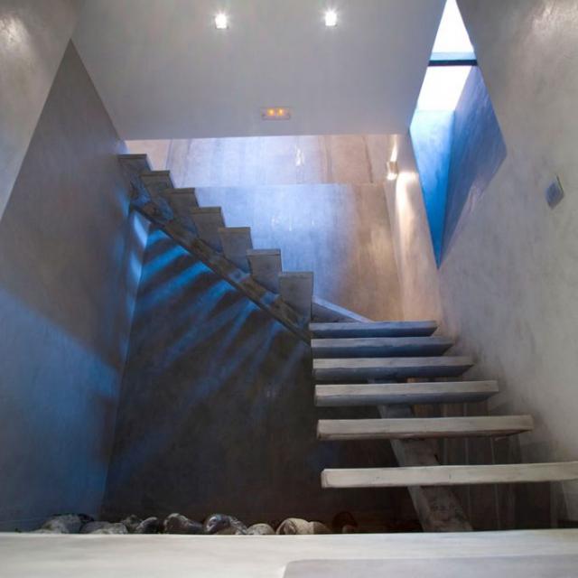 Scala in microcemento chiara con pareti grigie con sassi neri