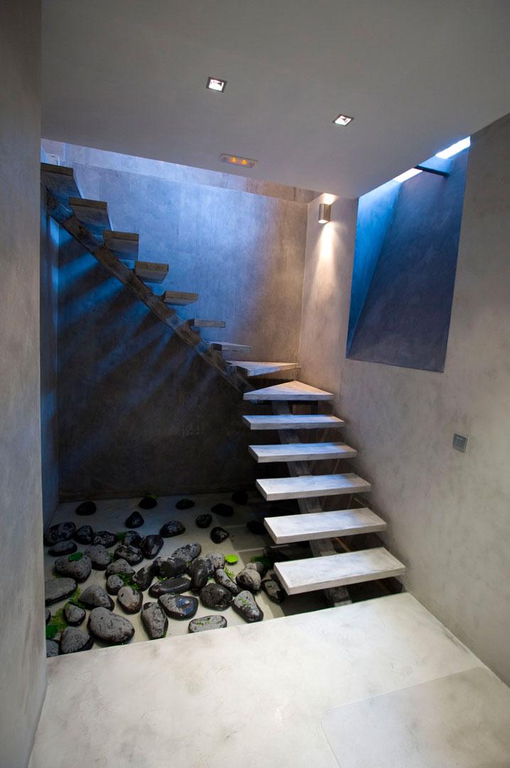 Scala in microcemento chiara con pareti grigie e sassi neri