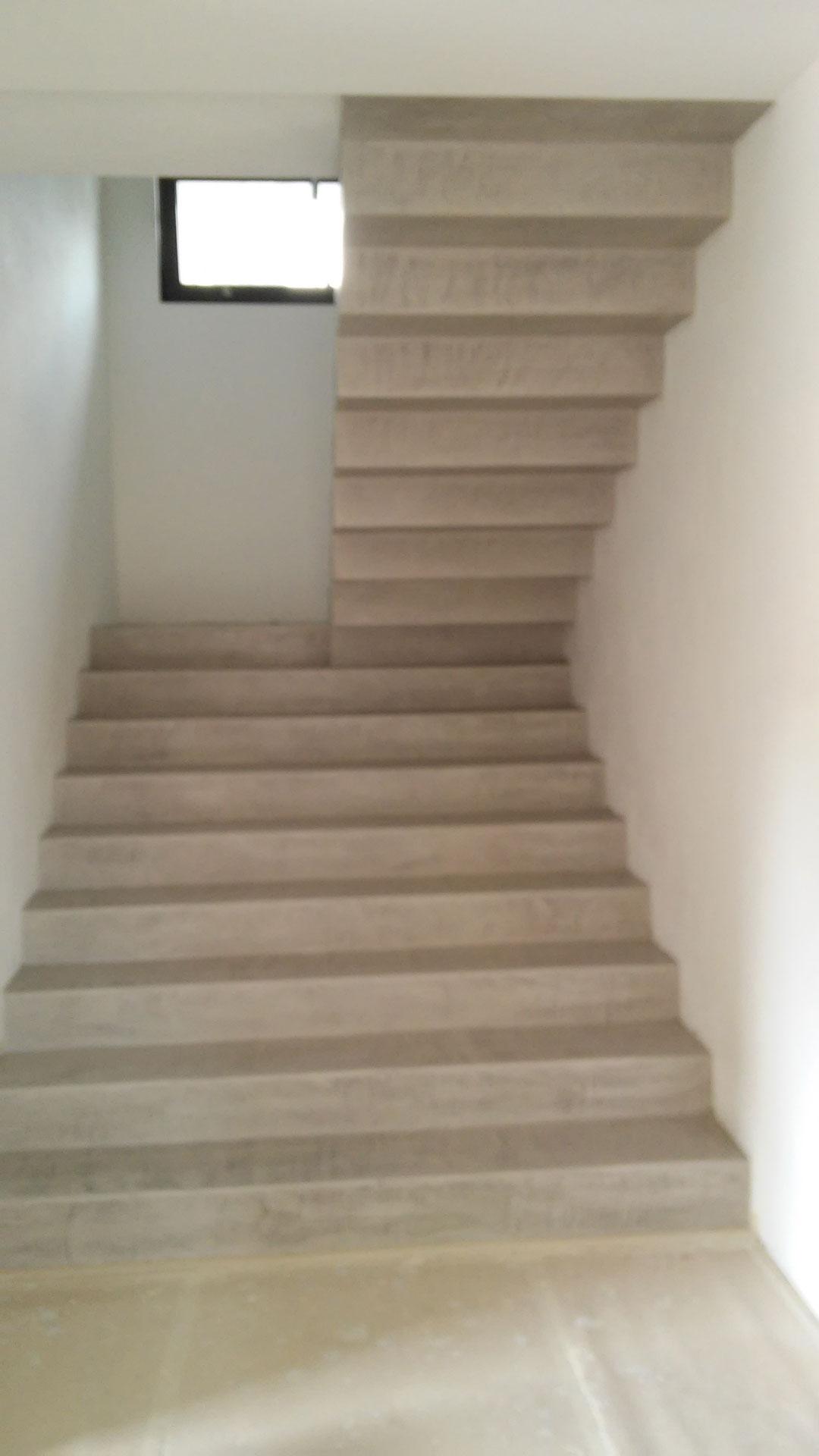 Scala in microcemento grigia con pareti bianche