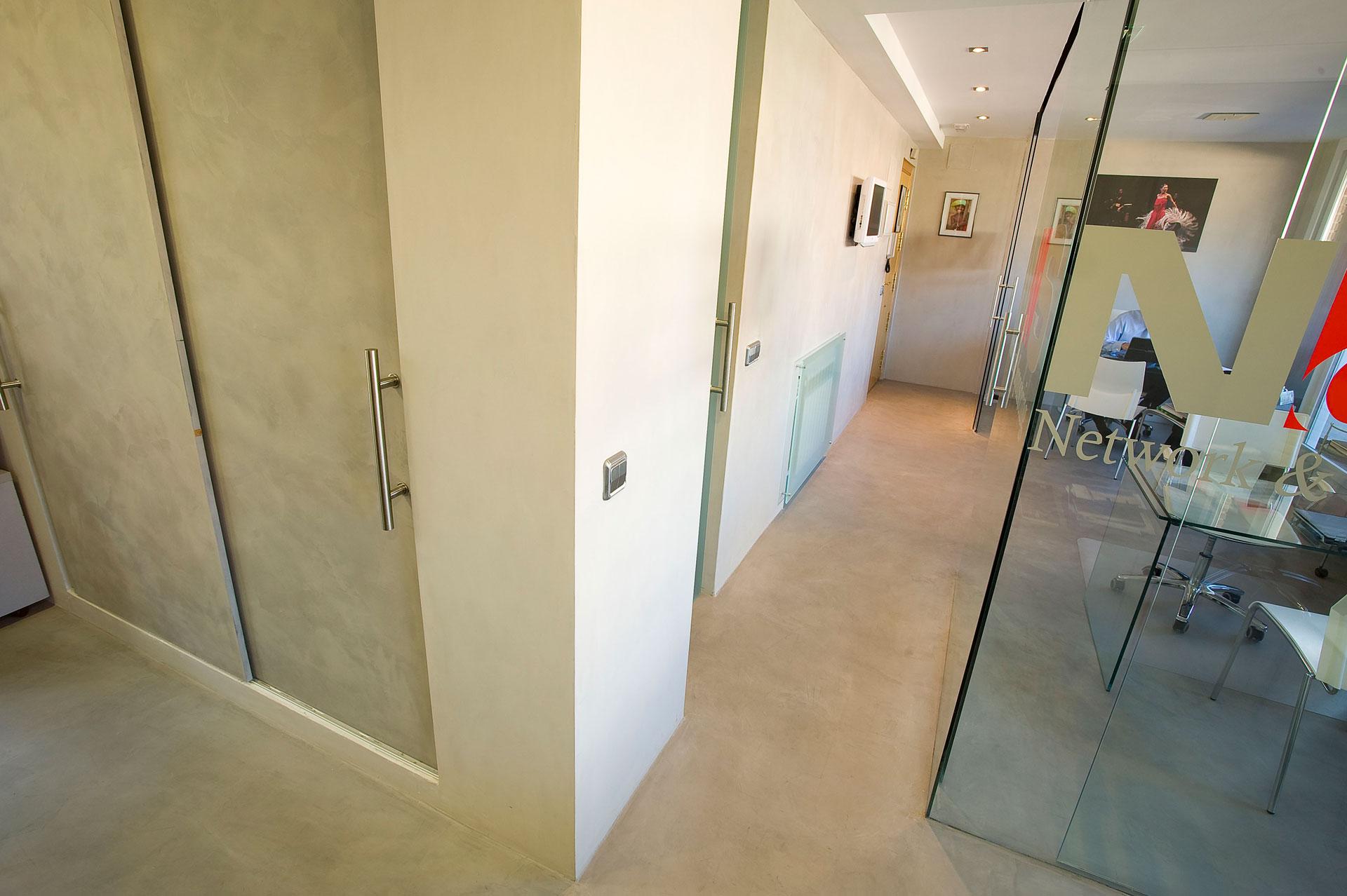Ufficio con pavimento e pareti in microcemento bianco