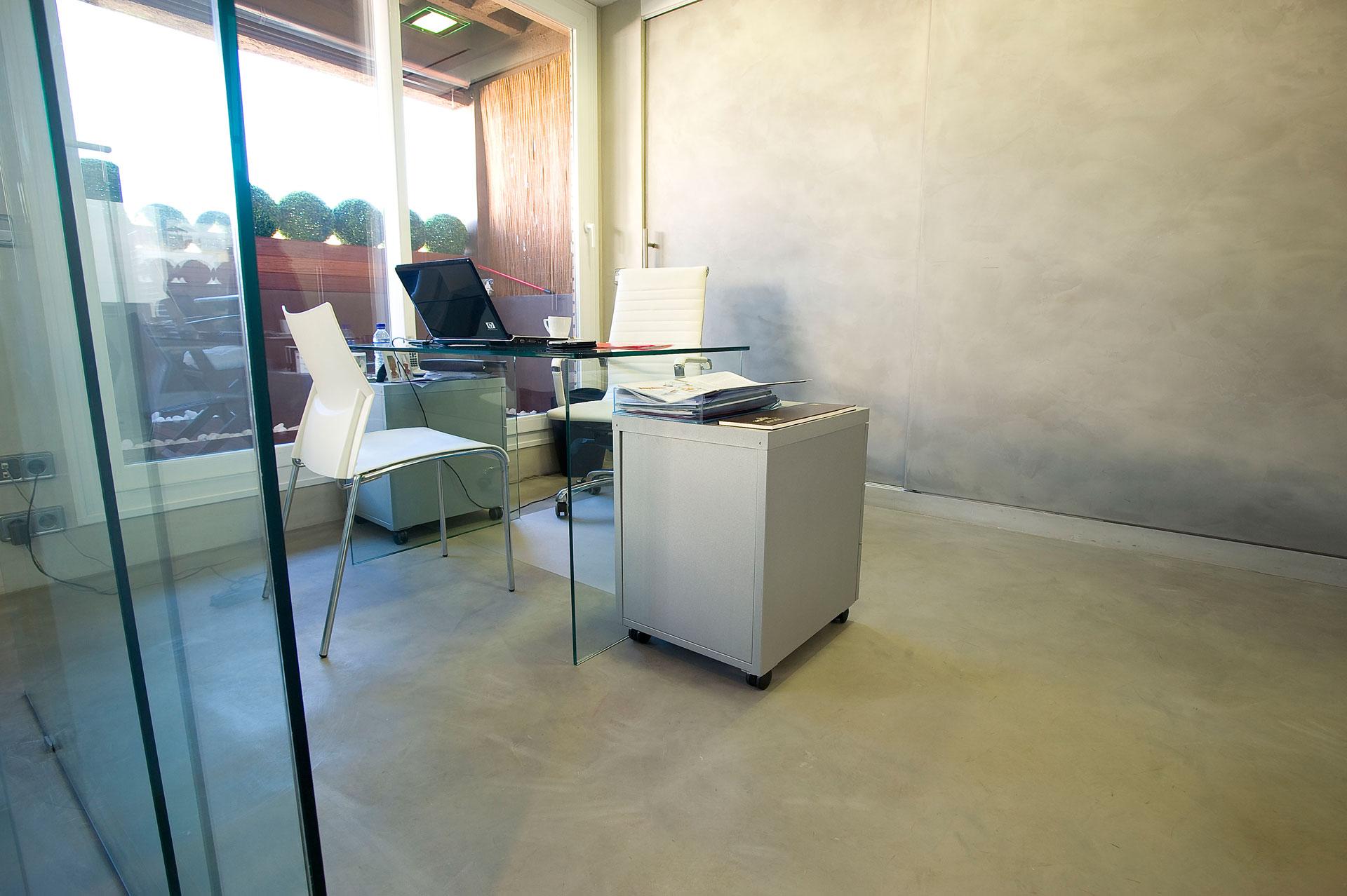 Ufficio con pavimento e pareti in microcemento bianco e scrivania in vetro