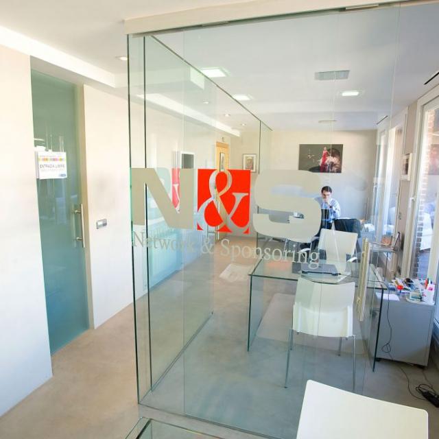 Ufficio con pavimento e pareti in microcemento bianco e separatori in vetro
