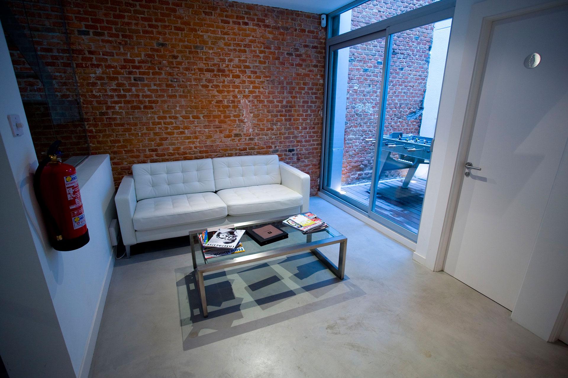Ufficio con pavimento in microcemento bianco e divano e tavolino