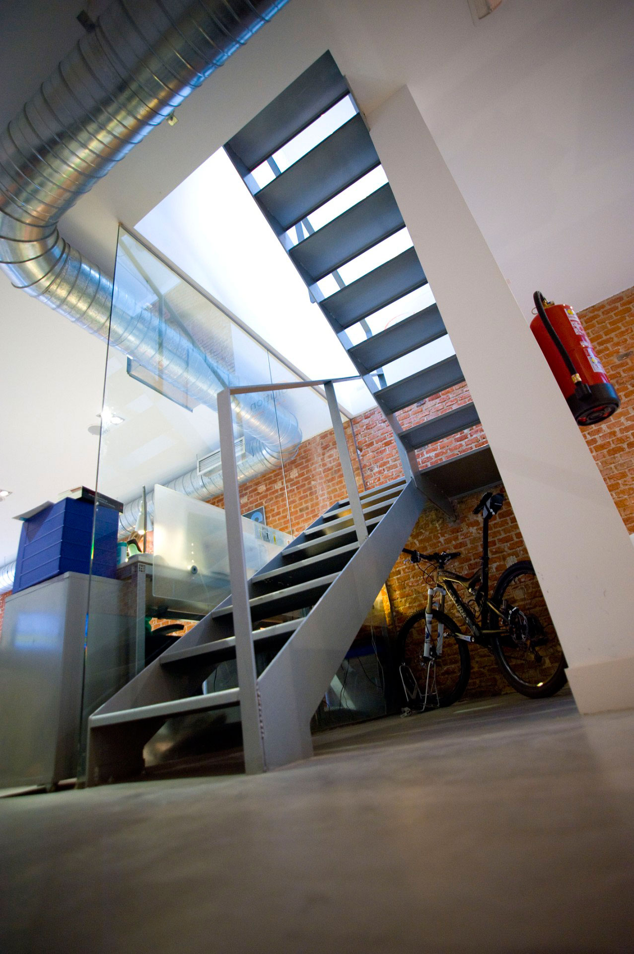 Ufficio con pavimento in microcemento, parete in mattoni e scala in ferro