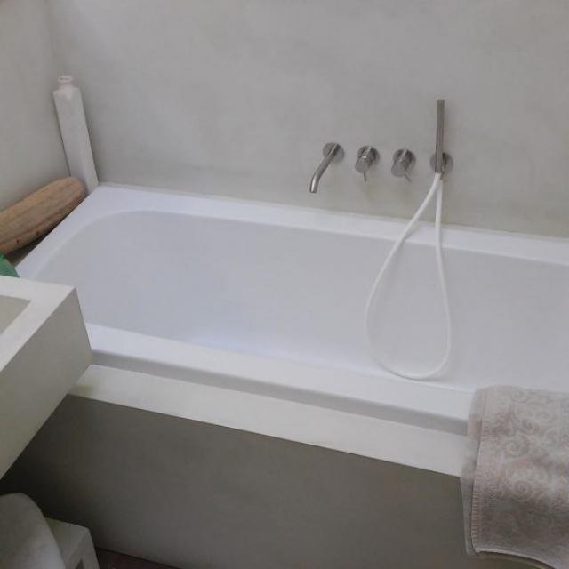 Bagno con lavandino e vasca in microcemento